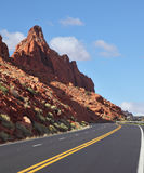 The marked  road passes between rocks Stock Images