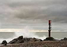 The Marker. A marker on the beach at Caister on sea standing strong as the waves crash over the rocks it highlights during high tides royalty free stock photo