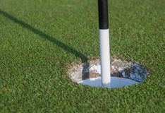 Marker in Golf Hole. A black and white marker points to the hole at the end of the course stock photography