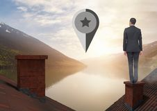 Marker location pointer and Businessman standing on Roofs with chimney and lake mountain landscape. Digital composite of Marker location pointer and Businessman Royalty Free Stock Photos