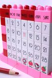 Marker Pencil and Lego Calendar. Pink Lego calendar with special day marked in pink, and a China marker pencil stock image