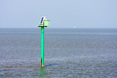 Marker pole with solar cells in the sea Stock Image