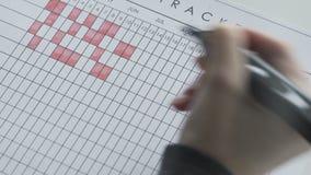 Markera dagar på en kalender vid den röda klädde med filt pennan arkivfilmer