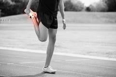 Markerade ben av idrottsman nen man sträckning på loppspår Royaltyfri Foto
