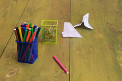 Markers in the blue box. Crayons in a yellow box. Sheets of paper and a pink marker on a yellow-green surface of the table Royalty Free Stock Images