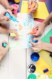Markers in male and female hands draw house and rain. On white paper. Artists wooden table with paints and colored paper. Hands hold colorful markers and draw stock photos