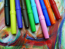 Markers on a painting. Colorful marker pens sit on an abstract painting Royalty Free Stock Photo