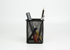 Markers, pen, pencil in black basket  on white backgroun Royalty Free Stock Image