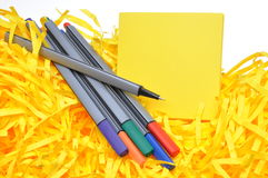 Markers with yellow sticky notes and shredded papers Stock Image
