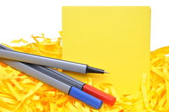 Markers with yellow sticky notes and shredded papers Royalty Free Stock Photography