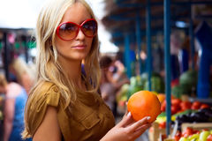 Market. A young girl with an orange on the southern market Royalty Free Stock Photos