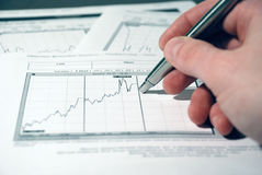 The market analyz. Man analyzes the schedule of the share market Stock Photo