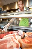 Market assistant picking meat Royalty Free Stock Image