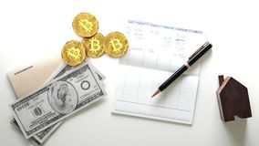 Four golden bitcoin coins, digital crypto currency, next to to a personal list of expenses and spendings royalty free stock photography