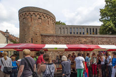 Market booth with shopping people in historic background Royalty Free Stock Photo