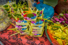 A market with a box made of leafs, inside an arrangement of flowers on a table, in the city of Denpasar in Indonesia.  stock photo
