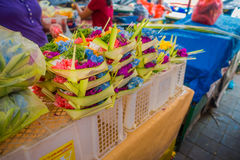 A market with a box made of leafs, inside an arrangement of flowers on a table, in the city of Denpasar in Indonesia.  royalty free stock image
