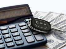 Market car concept. Modern key car calculator and 100 money dollars bills or banknotes. Market car concept. Modern key car on calculator and 100 money dollars stock photo