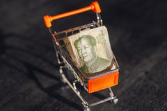 Market cart with a banknote of Chinese Yuan and face of leader Mao, as a symbol of modern international economy Stock Photos