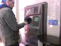 Young man using reverse vending machine Royalty Free Stock Image