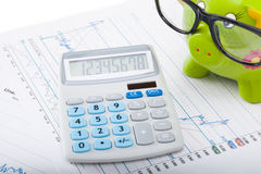 Market charts with green color piggy bank and calculator over it Royalty Free Stock Images