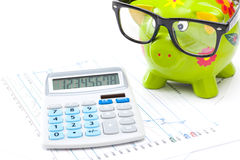 Market charts with piggy bank and calculator over it Royalty Free Stock Image