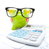 Market charts with piggy bank and calculator Royalty Free Stock Image