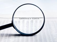 Market data words see through lens of loupe on financial newspaper Royalty Free Stock Photos