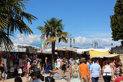 Market day in Lazise on the shore of Lake Garda. View of people visiting the local weekly street market at Lazise on the shore of Lake Garda in Italy on a hot Royalty Free Stock Photo