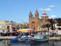 Market Day, Marsaxlokk in Malta. View across the crowded waters of the traditional fishing village of Marsaxlokk in Malta.  Colourful boats and architecture on a Stock Photos