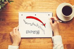 Market down trend chart with a person holding a pen stock photo