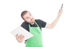 Market employee being busy multitasking with tablet and phones Royalty Free Stock Photo