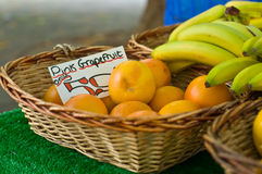 Market Fruit. An image showing bananas and pink Grapefruit in display baskets on a market stall stock photos
