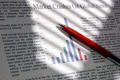 Market Goes Down. Selective focus closeup of fictitious news and graph indicating financial market downward movement with red pen, under dramatic lighting. ( Royalty Free Stock Photography