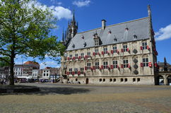 Market with the Gothic city Hall on a summer day in Gouda. Stock Photos