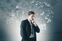 Market and idea concept. Thoughtful young european businessman with creative business sketch royalty free stock image