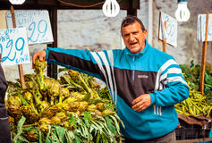 Market. PALERMO, ITALY - MARCH 13, 2015: Vendor sells artichokes at famous local market Ballaro in Palermo, Italy Royalty Free Stock Image