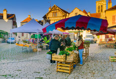 Market scene in the medieval village Noyers-sur-Serein. NOYERS-SUR-SEREIN, FRANCE - OCTOBER 12, 2016: Market scene with sellers and shoppers, in the medieval Stock Photography