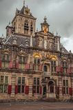 Market Square and Gothic City Hall building facade richly decorated on cloudy day in Delft. stock photography