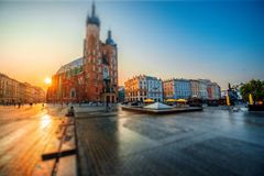 Market square in Krakow. Beautiful view on St. Mary's Basilica at the market square in Krakow on the sunrise. Wide angle view with tilt shift effect stock photo