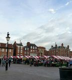 Market square in Newark, Nottinghamshire under grey autumn sky. Looking into the market Square of rural English town showing market stalls with red and white Stock Image