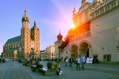Market square and St. Mary`s Basilica in Krakow, Poland in stunning sunset sun light. People tourists walking down the street and. Relaxing stock photography