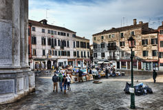 Market Square in Venice. Venice,Italy- February 18, 2012:People walking and opening the market stands in a Venetian market square in the morning, during the Stock Photography