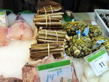 Razor clams, calmars, cuttlefish sepia, berberechos, palourdes on the market stall in Barcelona, Spain stock photography