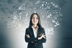 Market and start up concept. Attractive thoughtful young caucasian businesswoman with creative business sketch royalty free stock photo