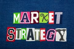 MARKET STRATEGY text word collage, multi colored fabric on blue denim, stock and investing concept. Horizontal aspect royalty free stock photography