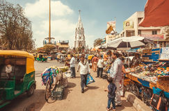 Market street with autos, clothing stores and rushing customers Royalty Free Stock Photography