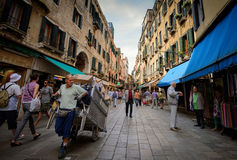 Market street in Venice. A man pulling a trolley with goods along the street in Venice Stock Images