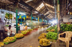 Market traders and buyers walk in motion blur in a storehouse with bananas and fruits Royalty Free Stock Photo
