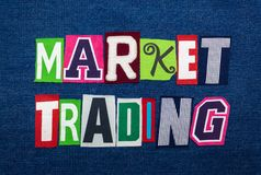 MARKET TRADING text word collage, multi colored fabric on blue denim, stock and investing concept. Horizontal aspect stock image